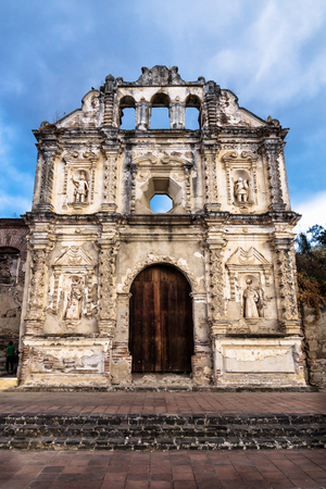Church fassade ruin of Ermita de Santa Isabel with dramatic blue cloudscape vertical, Antigua, Guatemala Stock Photo