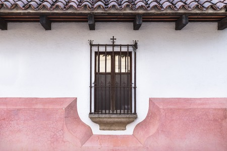 Caged window in colonial style with cross decoration in Antigua, Guatemala
