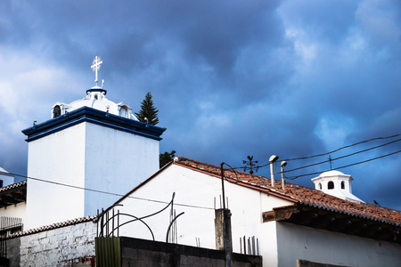 Modern white churchtowers on dramatic blue cloudscape in Antigua, Guatemala