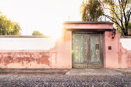 Finca port in colonial style with rose wall and sunbeam in Antigua, Guatemala Stock Photo
