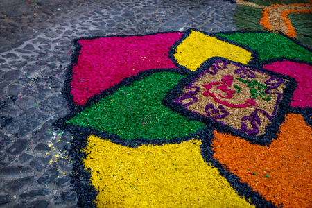 Sawdust alfombra with flower design for Semana Santa on cobbled street, Antigua, Guatemala