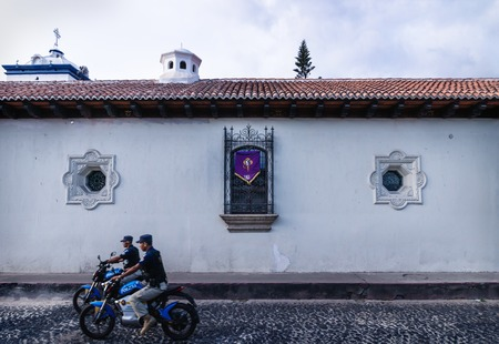 Antigua, Guatamala - 23 March 2018: Police on motorbikes passing by a colonial house with Semana Santa decoration