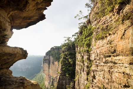 Rock formations, cliffs and canyons along the Three Sisters with view to Echo Point with backlight, Katoomba, New South Wales, Australia