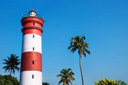Alleppey Lighthouse with red and white stripes with palm trees on cloudless blue sky, Aleppuzha, Kerala, India