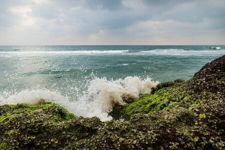 Splash of wave along coastside on volcanic stones of Varkala with dark cloudscape, India