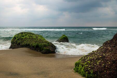 Splash of wave along coastside on green moss volcanic stones of Varkala with dark cloudscape, India Reklamní fotografie