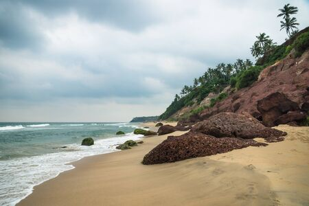 Cliff of Varkala along the coast with red volcanic stones and cloudscape, India
