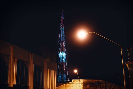 Transmitter tower decorated with lights as christmas tree with colonial building and street lights, Merida, Yucatan, Mexico