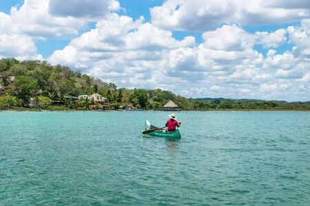 El Remate, Peten, Guatemala - 29 May 2019: Fisherman in canoe boat in turquoise colored lake Itza rowing towards village with sunny cloud sky