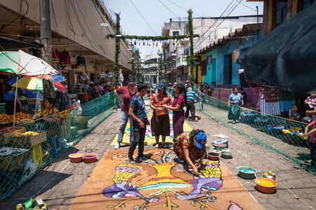 Santiago Atitlan, Guatemala - 30 March 2018: Local people making alfombra, colorful sawdust carpets for Semana Santa, Easter on the street next to market Editorial
