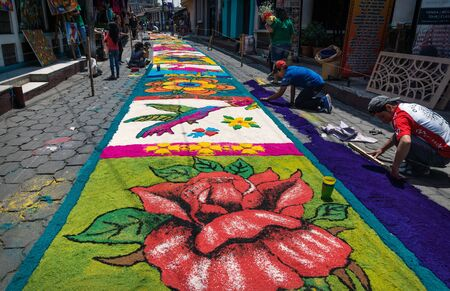 Santiago Atitlan, Guatemala - 30 March 2018: Local people making hummingbird alfombra, colorful sawdust carpets for Semana Santa, Easter on the street
