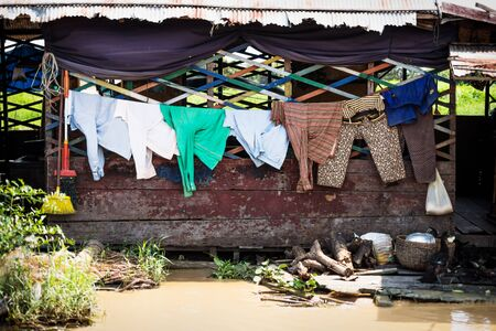 Laundry on a wooden floating house in poor village at Tonle Sap Lake in Puok, Siem Reap Province, Cambodia