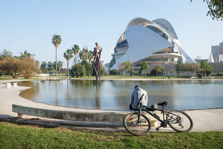 Valencia, Spain - 17 February 2020: Man reading at pond inf front of Palau des Arts Reina Sofia in the City of Arts and Sciences designed by architects Santiago Calatrava and Felix Candela