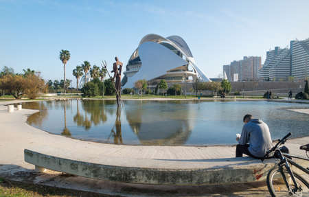 Valencia, Spain - 17 February 2020: Man sitting at pond at Palau des Arts Reina Sofia in the City of Arts and Sciences designed by architects Santiago Calatrava and Felix Candela