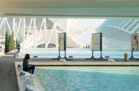 Valencia, Spain - 17 February 2020: Female tourist sitting at the pond of the City of Arts and Sciences designed by architects Santiago Calatrava and Felix Candela 에디토리얼