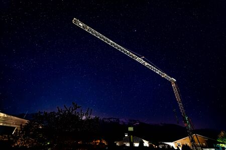 Crane over houses during dark cloudless night with stars with snow mountains