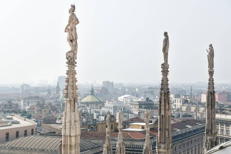 Statues of the dome looking over the cityscape of Milan, Italy on a cloudless sunny day