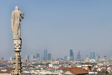 Statue of the dome looking over the modern cityscape of Milan, Italy on a cloudless sunny day