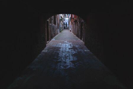 Empty Dark alley behind arch in Venice, Italy