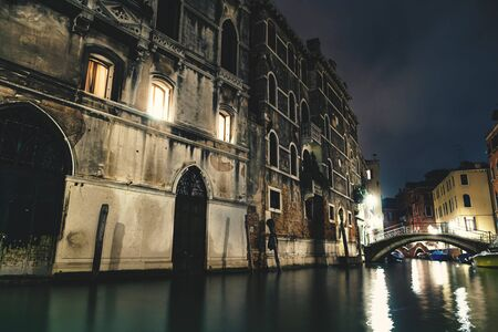 Small canal with little bridge along historic buildings with bright shining light out of the windows at night in Venice, Italy Stock Photo