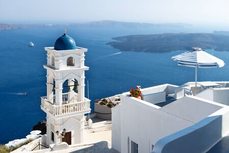 The tower of Anastasi church and parasol with ocean and islands in the background on a sunny cloudless day, Imerovigli, Santorini, Greece