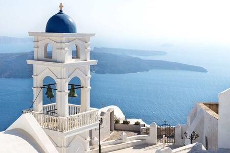 The bell tower of Anastasi church with ocean and islands in the background on a sunny cloudless day, Imerovigli, Santorini, Greece Stock Photo