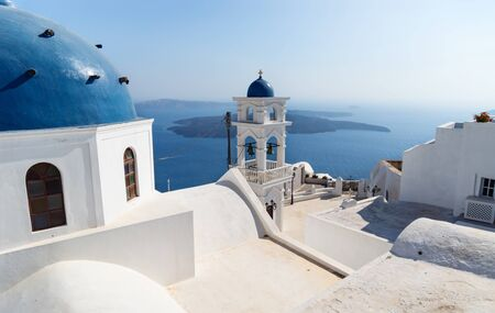 The dome and tower of Anastasi church with ocean and islands in the background on a sunny cloudless day, Imerovigli, Santorini, Greece