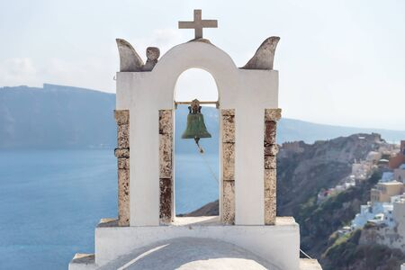 Bell tower with view on cliffs, blue ocean and village of Oia, Santorini, Greece Stock Photo