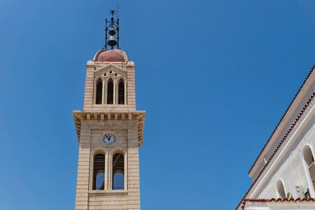 Detail of the Megalos Antonios church bell tower with clock on blue cloudless sky in Rethymnon, Crete, Greece Stock Photo