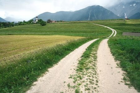 Winding path through grass and farm fields with Austrian Alps and stormy weather, Mieminger Plateau, Tyrol, Austria