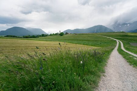 Dirt road through farmland to village with Austrian Alps and stormy weather, Mieminger Plateau, Tyrol, Austria