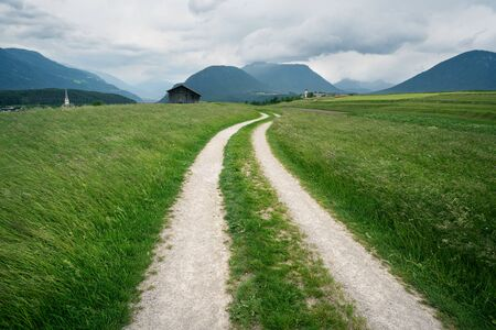 Winding path through grass meadows to villages with churches with Austrian Alps and stormy weather, Mieminger Plateau, Tyrol, Austria