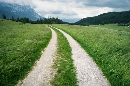 Winding path through blown grass meadows with Austrian Alps and stormy weather, Mieminger Plateau, Tyrol, Austria Stock Photo
