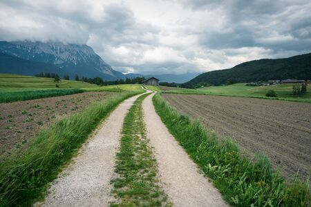 Winding path through farmland with Austrian Alps and stormy weather, Mieminger Plateau, Tyrol, Austria Stock Photo