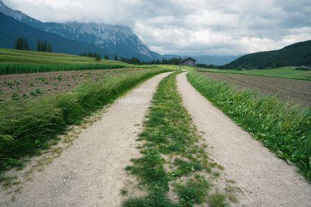 Winding path through agricultural fields with Austrian Alps and stormy weather, Mieminger Plateau, Tyrol, Austria Stock Photo