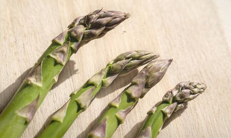 Close up of fresh green aspargus heads on a wooden kitchen boad with bright light Stock Photo