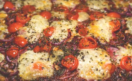 Close up of a tasty pizza with fresh mozzarella, tomatoes red onion and oregano home made