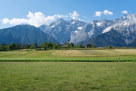 Green meadows along the rocky mountain range with typical small Austrian church at sunny summer day, Mieming, Austria