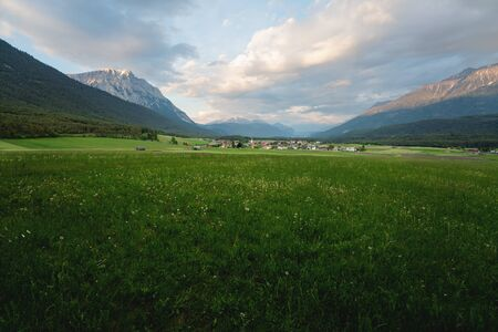 Panoramic view over flower meadow to the village of Wildermieming during sunset, Tyrol, Austria