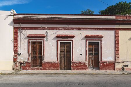 Facade of typical Mexican abandoned colonial building wth wooden doors in Merida, Yucatan, Mexico