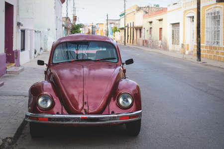 Merica, Yucatan, Mexico - 28 October 2018 - Red Oldtimer Volkswagen Beetle in the colonial historical streets