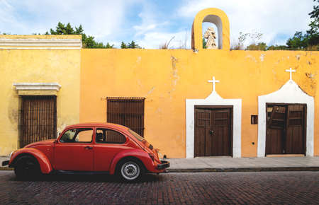 Merica, Yucatan, Mexico - 28 October 2018 - Red Oldtimer Volkswagen Beetle in the colonial historical streets at 'Casa Culcal Kin'