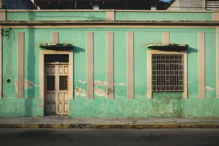 Facade of typical Mexican green abandoned colonial building in Merida, Yucatan, Mexico Stock Photo