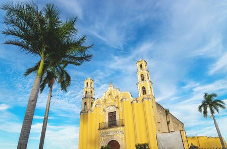 Colonial church 'SAN Juan Bautista' in the colonial center of Merida with palm trees during last sun on blue sky, Yucatan, Mexico