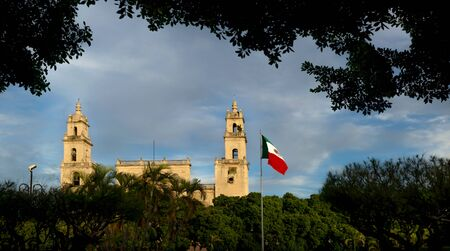 Facade of the cathedral of Merida 'San Ildefonso' and waving Mexican flag during last sun, Merida, Yucatan, Mexico Stock Photo