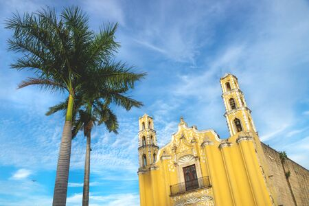 Colonial church 'SAN Juan Bautista' in the colonial center of Merida during last sun on blue sky, Yucatan, Mexico