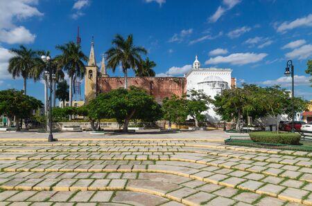Santa Ana park and church with tropical trees with sunny blue sky, Merida, Yucatan, Mexico