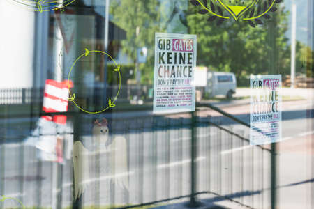 Mieming, Austria - 1 June 2020: Papers in a store window protesting against forced vaccination and Bill Gates 'Gibt Gates keine Chance' - German for Don't give Gates a chance Editorial