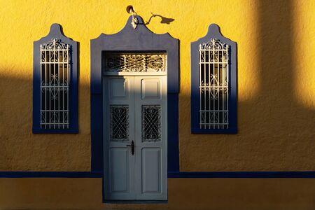 Sunlit facade of colorful colonial building with beautiful shadows in Merida, Yucatan, Mexico