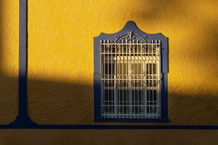 Sunlit facade of colorful colonial window with beautiful shadows in Merida, Yucatan, Mexico